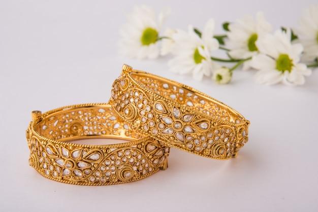 Indiase traditionele huwelijksjuwelen, armbanden met huldi kumkum en witte bloemen. selectieve focus