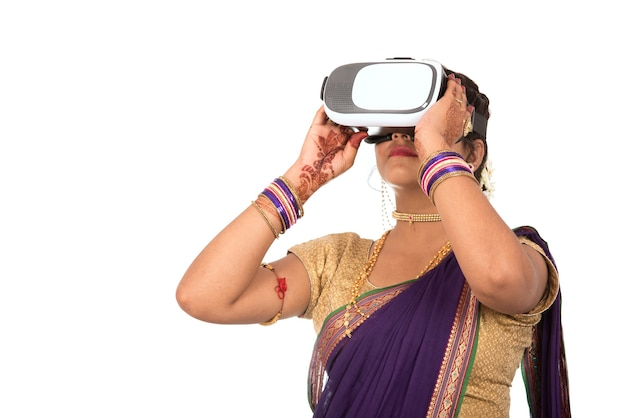 Indiase traditionele jonge vrouw in saree die hoewel vr-apparaat kijkt