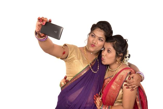 Indiase traditionele meisjes nemen selfie met smartphone op wit