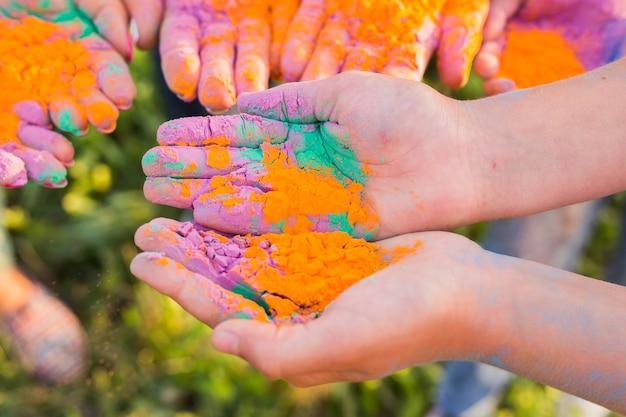 Indiase vakantie, plezier, festival van holi en mensenconcept - vrouwelijke handen met veelkleurig poeder