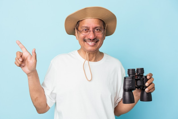 Indiase visser van middelbare leeftijd die een hengel vasthoudt op een blauwe achtergrond die glimlacht en opzij wijst en iets op de lege ruimte laat zien.