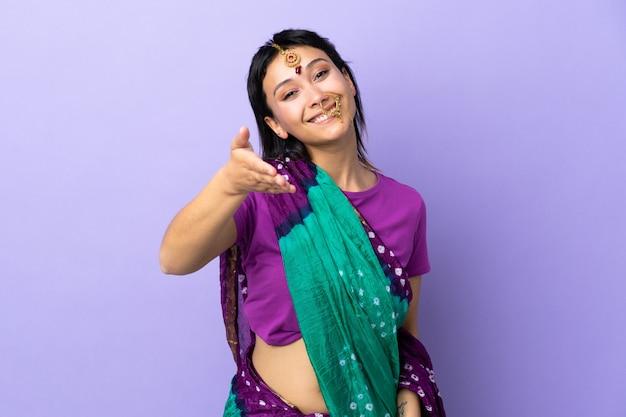 Indiase vrouw geïsoleerd op paars handen schudden voor het sluiten van een goede deal
