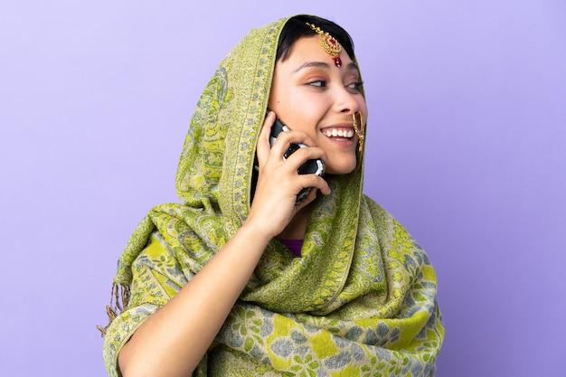 Indiase vrouw geïsoleerd op paars houden een gesprek met de mobiele telefoon met iemand