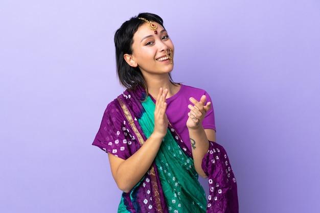 Indiase vrouw geïsoleerd op paarse achtergrond applaudisseren na presentatie in een conferentie