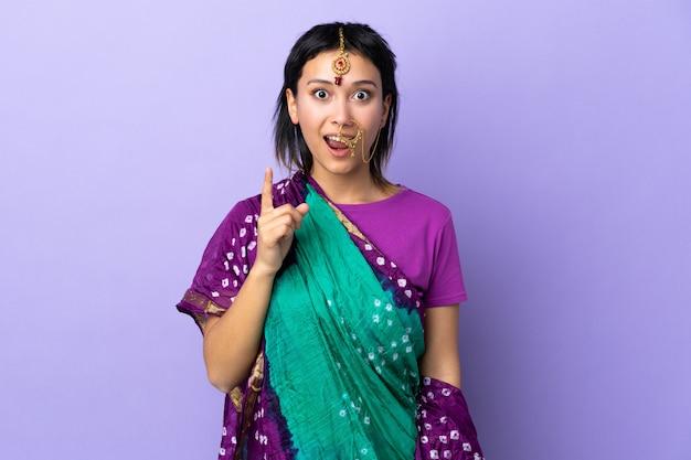Indiase vrouw geïsoleerd op paarse muur van plan om de oplossing te realiseren terwijl het opheffen van een vinger