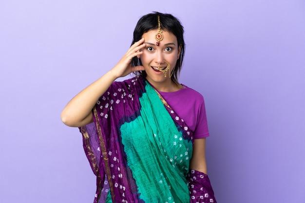 Indiase vrouw geïsoleerd op paarse ruimte heeft iets gerealiseerd en van plan de oplossing
