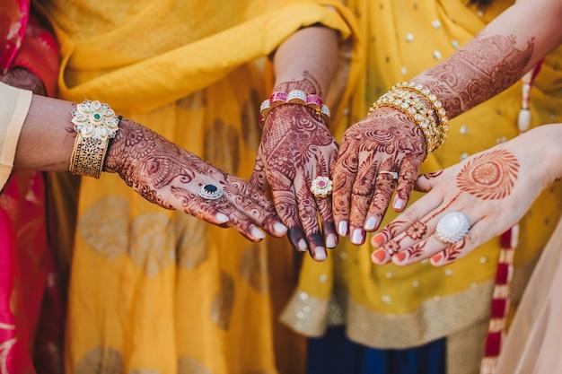 Indiase vrouw houdt haar handen bedekt met mehndi en draagt armbanden achter haar borst
