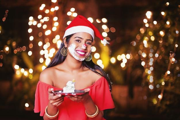Indiase vrouw in nieuwjaarspet met cakeroom over haar gezicht geslagen