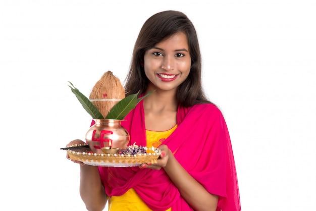 Indiase vrouw met een traditionele koperen kalash met pooja thali, indian festival, koperen kalash met kokos en mangoblad met bloemendecoratie, essentieel in hindu pooja.