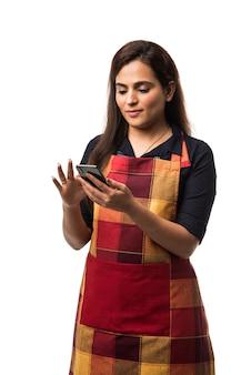 Indiase vrouw of vrouwelijke chef-kok in schort die smartphone gebruikt terwijl hij geïsoleerd staat op een witte achtergrond
