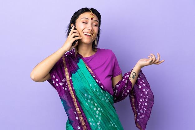 Indiase vrouw op paarse muur houden van een gesprek met de mobiele telefoon met iemand