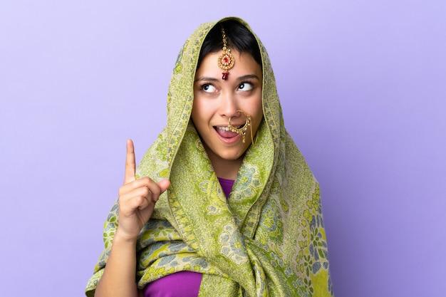 Indiase vrouw op paarse muur van plan om de oplossing te realiseren terwijl het opheffen van een vinger