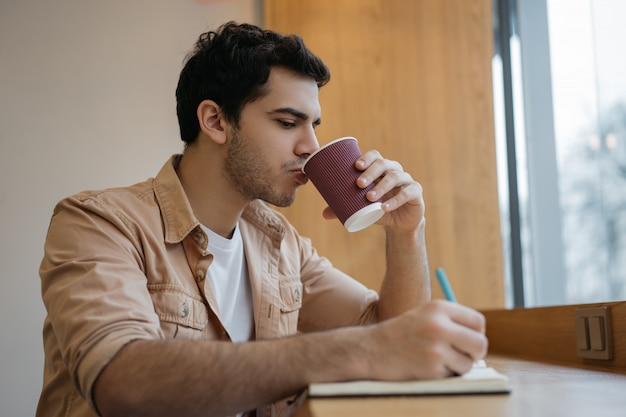 Indiase zakenman koffie drinken in café, het maken van aantekeningen, planning opstarten
