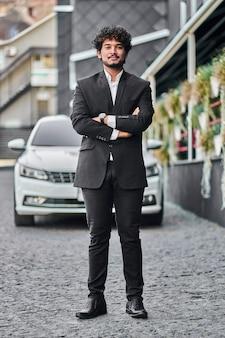Indiase zakenman op de achtergrond van een auto.