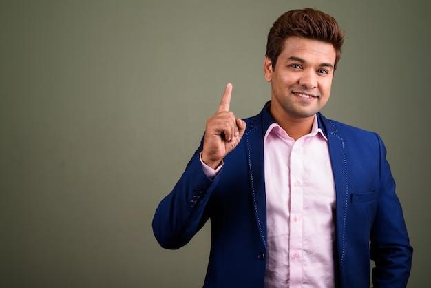Indiase zakenman pak dragen tegen gekleurde achtergrond