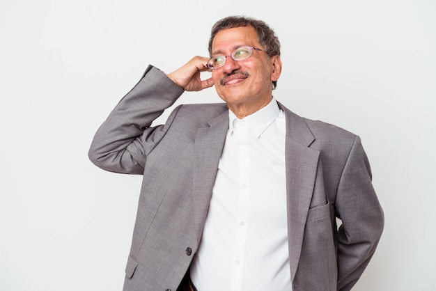 Indiase zakenman van middelbare leeftijd geïsoleerd op een witte achtergrond die de achterkant van het hoofd aanraakt, denkt en een keuze maakt.