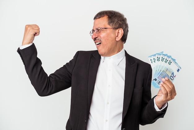 Indiase zakenman van middelbare leeftijd met rekeningen geïsoleerd op een witte achtergrond die vuist opheft na een overwinning, winnaarconcept.