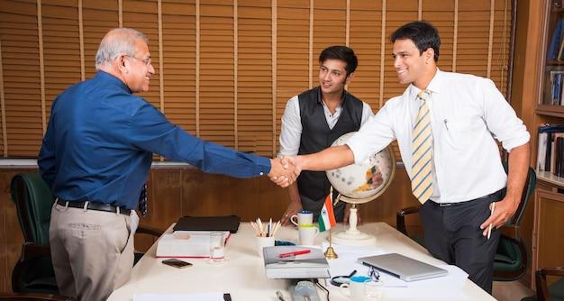 Indiase zakenmensen in bedrijfscultuur werken op kantoor handen schudden om een deal te sluiten