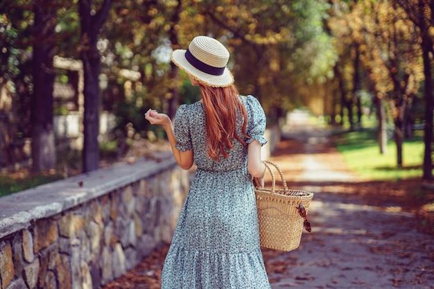 Indiase zomer achterkant van roodharige vrouw loopt in het park draagt in fladderende jurk kijkt zijwaarts