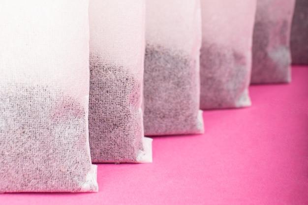 Indiase zwarte theezakjes close-up op roze achtergrond