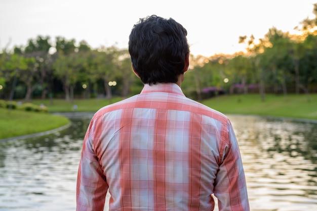 Indier die schilderachtig uitzicht op het meer in vreedzaam groen bekijkt