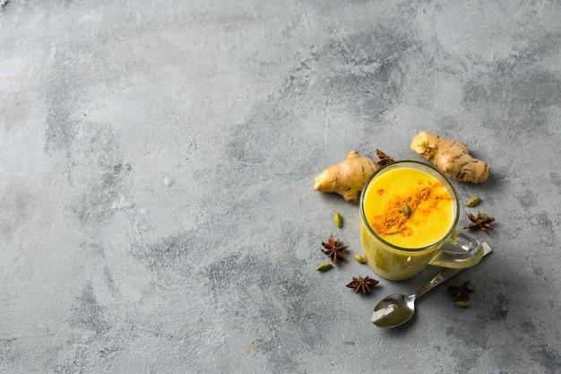 Indiër drinkt kurkuma gouden melk in glas. gouden latte met ingrediënten voor het koken.