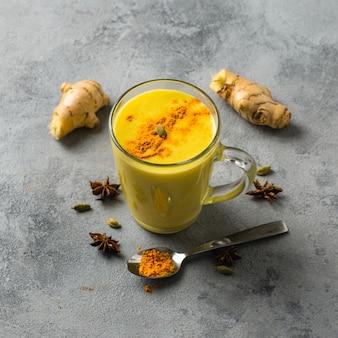 Indiër drinkt kurkuma gouden melk in glas. gouden latte op lichte achtergrond met ingrediënten voor het koken