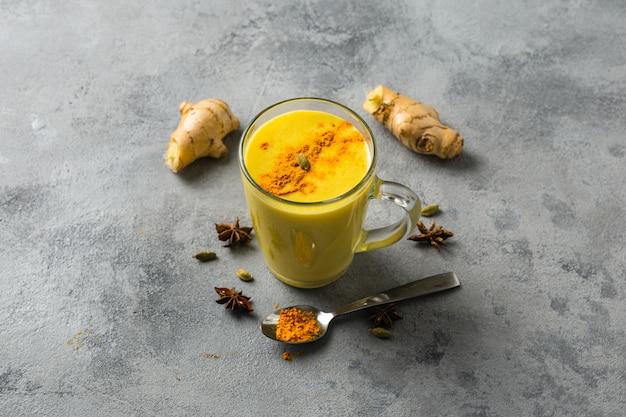 Indiër drinkt kurkuma gouden melk in glas. gouden latte op lichte tafel met ingrediënten voor het koken