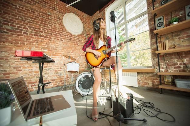 Indierock. mooie vrouw in koptelefoon die muziek opneemt, zingt en gitaar speelt terwijl ze op de loft-werkplek of thuis zit. concept van hobby, muziek, kunst en creatie. eerste single maken.