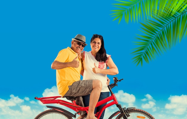 Indisch aziatisch gepensioneerd stel met hun fiets of fiets op het strand, humeurig effect