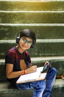 Indisch / aziatisch jongetje dat online studeert met behulp van mobiele telefoon thuis