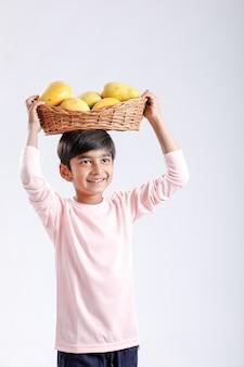 Indisch / aziatisch jongetje mango mand in de hand houden
