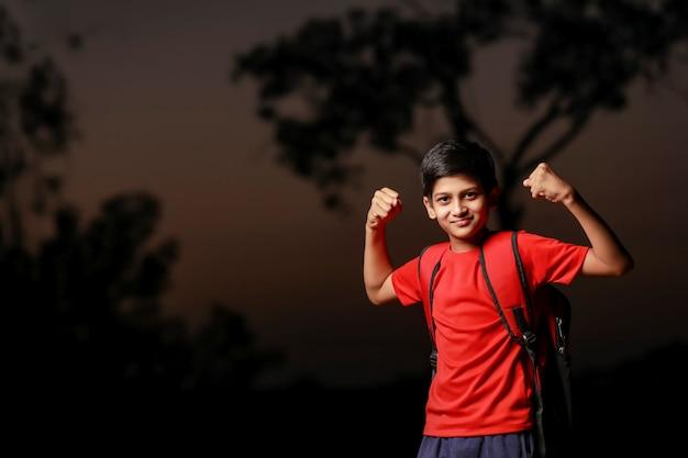 Indisch blij en opgewonden kind dat winnaargebaar met opgeheven wapens doet
