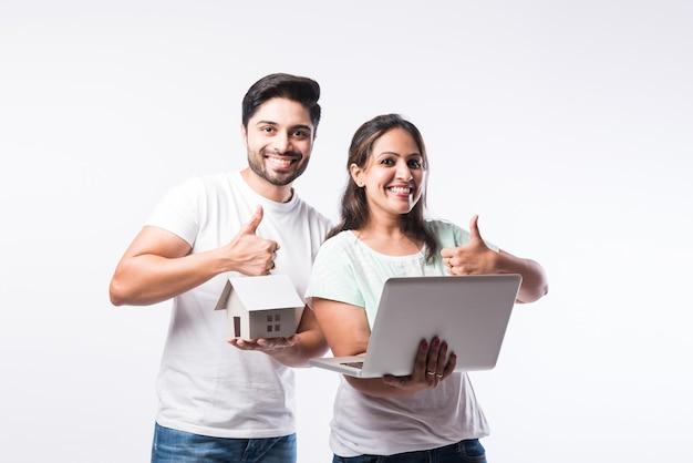 Indisch jong familiepaar dat nieuw huis online kiest, onroerend goed zoekt om te kopen of te huren, huis te koop op het scherm van de computer, staande tegen een witte achtergrond