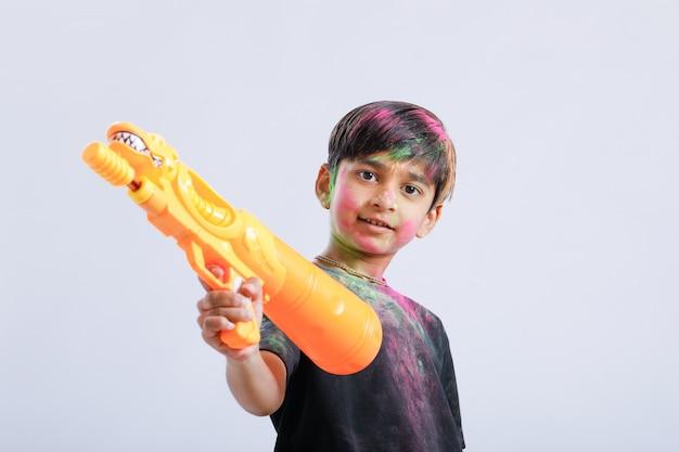 Indisch kind dat holi met kleurenkanon speelt
