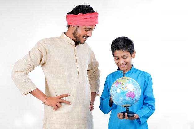 Indisch kind dat wereldbol in de hand houdt en zijn vader die wat informatie geeft.