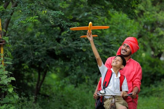 Indisch kind speelt met speelgoed vliegtuig met zijn vader op cyclus