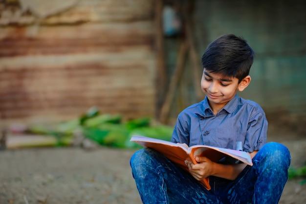 Indisch landelijk kind dat een boek leest