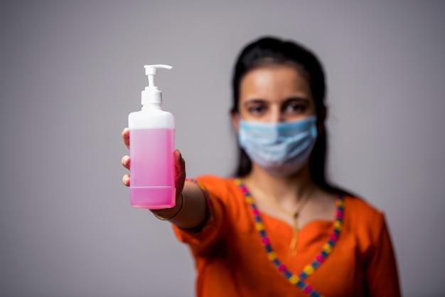 Indisch meisje dat handendesinfecterend middel toont dat medisch masker draagt. handen wassen antiseptisch. corona virus-concept