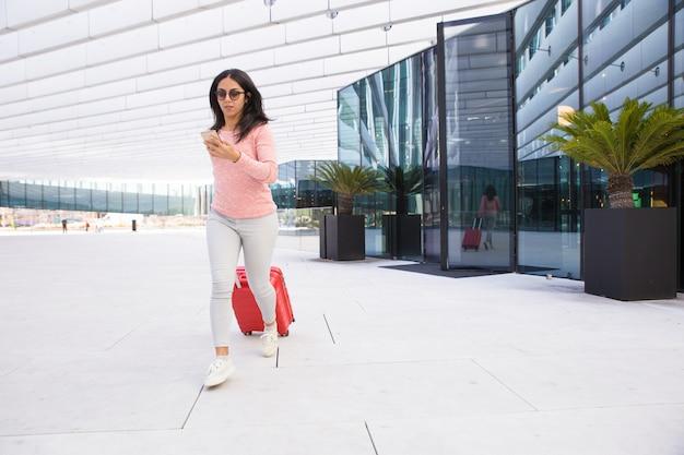 Indisch meisje die bagage op wielen dragen en aan luchthaven lopen