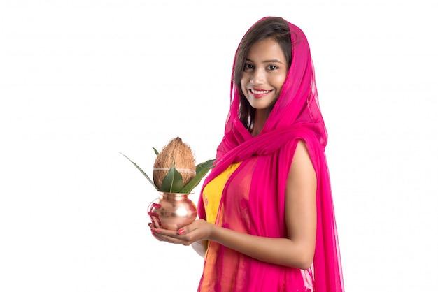 Indisch meisje met een traditionele koperen kalash, indian festival, koperen kalash met kokosnoot en mangoblad met bloemendecoratie, essentieel in hindoe pooja.