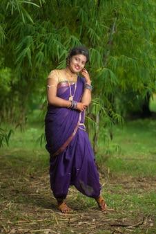 Indisch mooi jong meisje in traditionele saree poseren buitenshuis