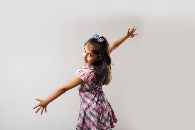 Indisch schattig klein meisje met beide handen uitgespreid als vleugels tegen een witte achtergrond.