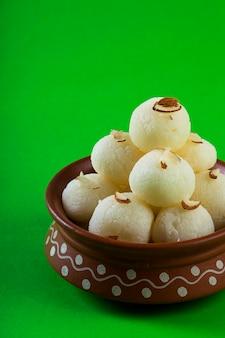 Indisch snoepje of dessert - rasgulla, beroemd bengaals snoepje in kleikom op groene achtergrond
