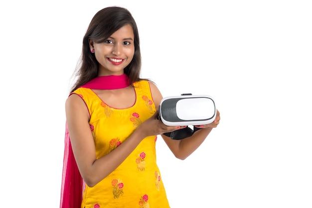 Indisch traditioneel jong meisje dat en vr-apparaat houdt toont