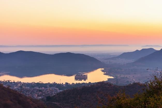 Indisch uitzicht, zonsopgang op het man sagar-meer en het jal mahal-paleis in jaipur.