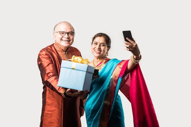 Indisch vrolijk oud stel dat verjaardag viert met chocoladetaart terwijl ze etnische traditionele kleding dragen
