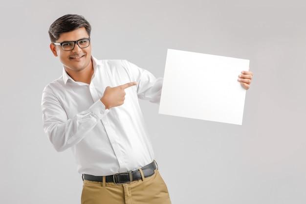 Indische aziatische jonge mens die leeg uithangbord op witte achtergrond toont