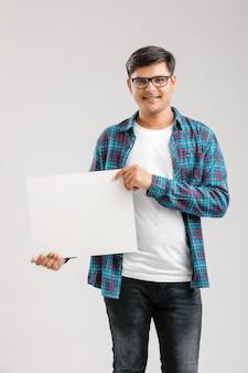 Indische, aziatische jonge mens die leeg uithangbord toont