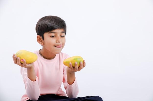 Indische / aziatische kleine jongen die mango eet